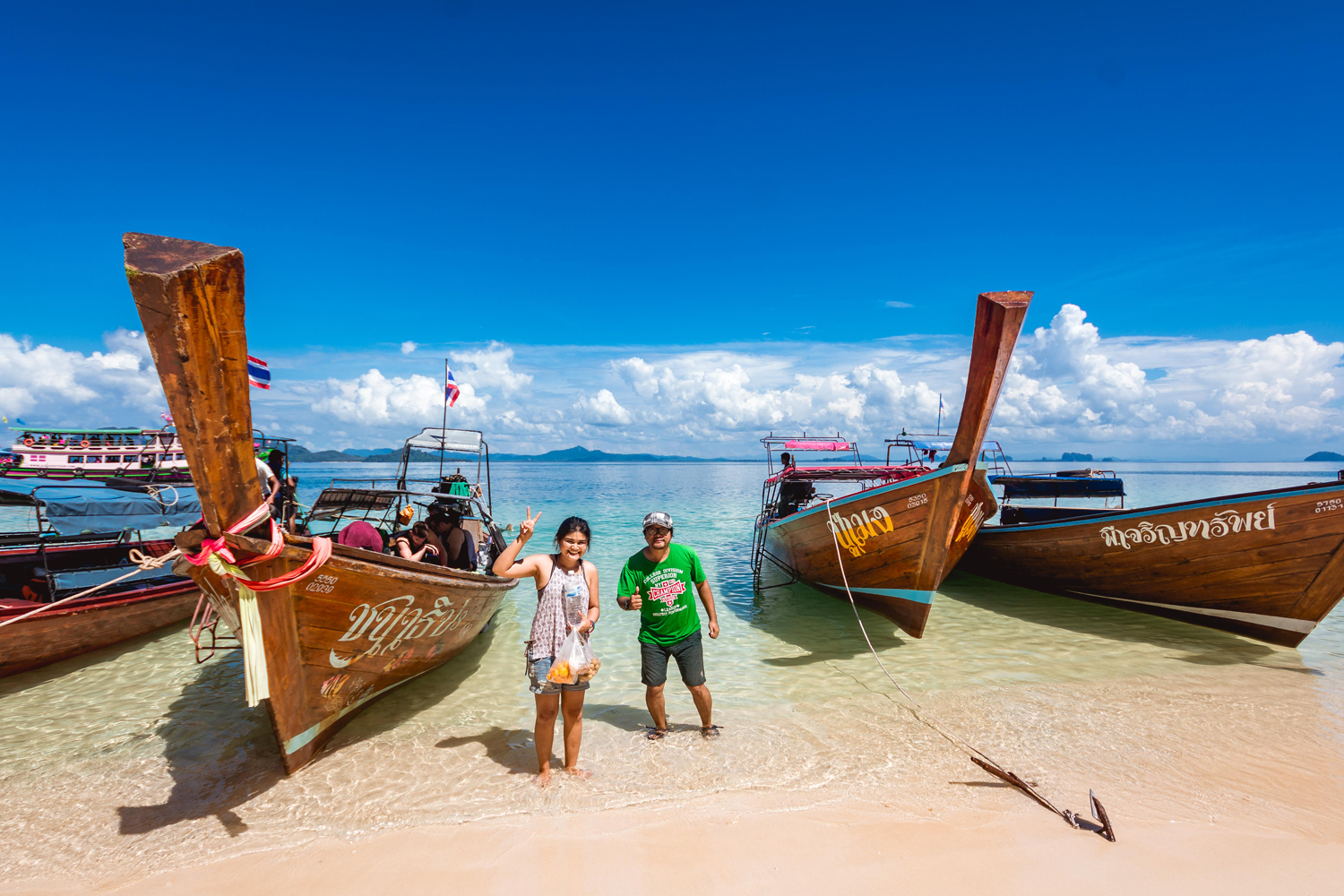 A Road Experience staff member and a volunteer cameraman pose in front of park boats beached on one the Trang islands